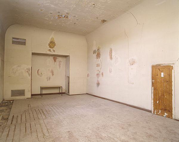 Blick in den Ritualraum im Jahr 2010. Auf der linken Seite ist die ehemalige Altarnische zu sehen, durch eine Sondierungsfreilegung ist am Giebel bereits das freimaurerische Emblem Zirkel und Winkelmaß zu erkennen. Auch an der Decke sind erste Freilegungen erfolgt