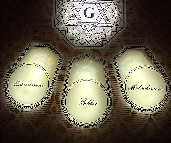 Die Glasscheibe in der Altarnische des ehemaligen Ritualraums mit den Schriftzügen Mikrokosmos – Biblia – Makrokosmos
